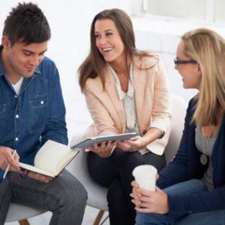 Produktbild für Berufshoroskop: 3 junge Leute scherzen ausgelassen miteinander während eines informellen Geschäftsmeetings