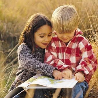 Produktbild zu Persönliches Kinderhoroskop: Ein Junge und ein Mädchen sitzen in einem Feld und schmökern in einem Atlas